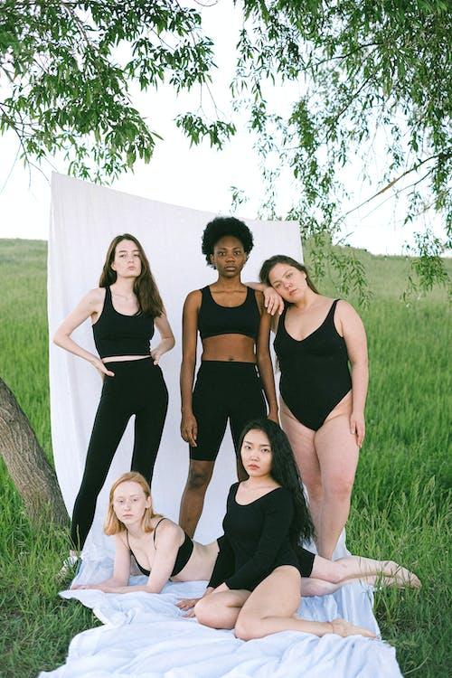 3 Women in Black Tank Top Standing on Green Grass Field