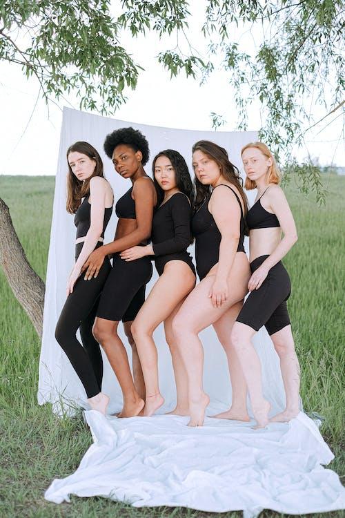 Group of Women in Black Dresses Posing for Photo