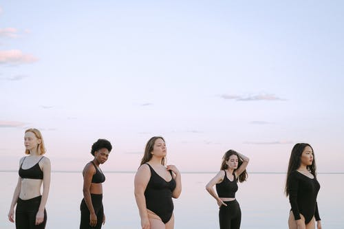 3 Women in Black and White Tank Top Standing on White Sand
