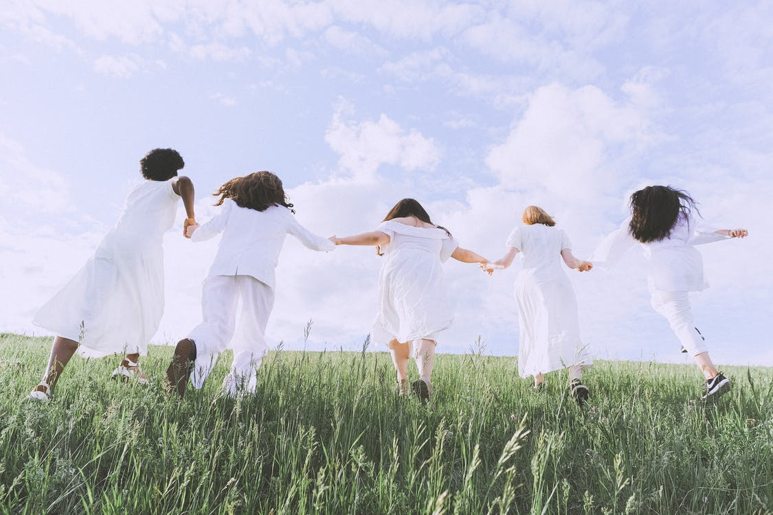 Women in White Dress Running on Green Grass Field
