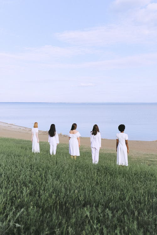 Women in White Dresses Standing on Green Grass Field Near Body of Water