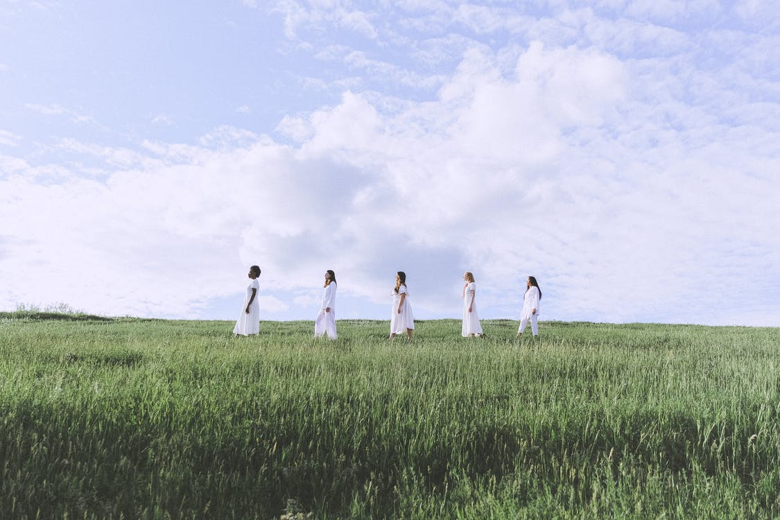 *+&*Women in White Dresses Standing on Green Grass Field Under Cloudy Sky