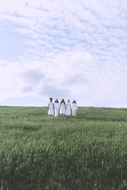 Family Standing on Green Grass Field Under White Clouds