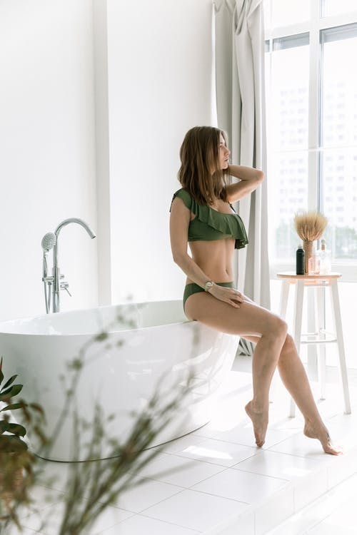 Woman in Green Bikini Sitting On Bathtub