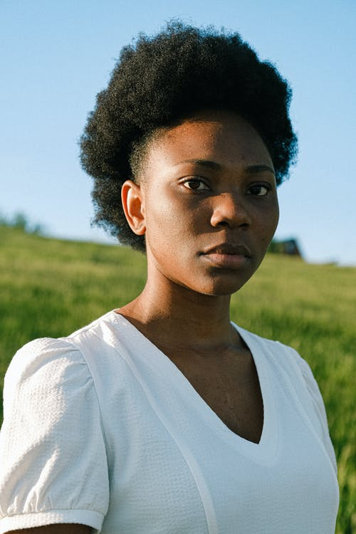 natural hairstyles for work: Woman in White Crew Neck Shirt Standing on Green Grass Field