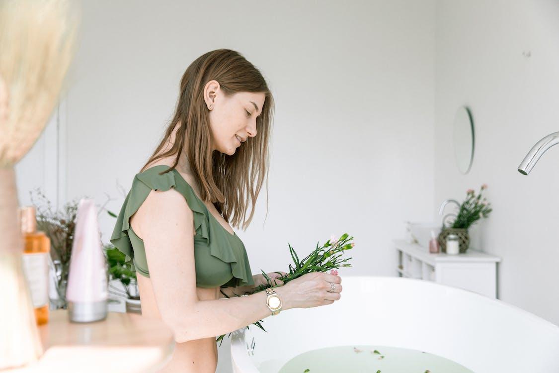 Woman in Green Bikini Holding Small Flowers