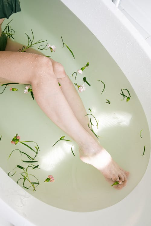 Persons legs in a bathtub filled with water, flowers floating in the water