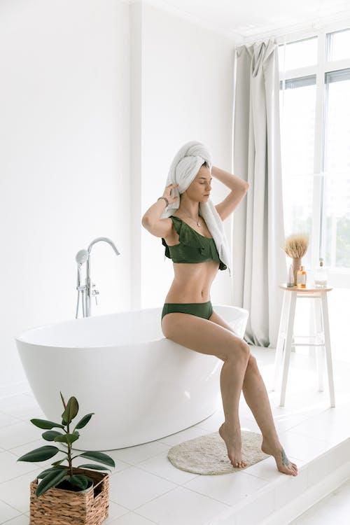 Photo Of Woman Sitting On Edge Of Bathtub