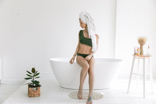 Photo Of Woman Sitting On The Edge Of Bathtub