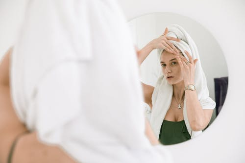Woman Standing In front Of A Mirror Applying Cream On Her Face
