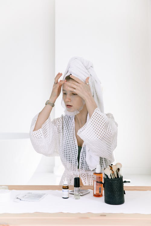 Photo Of Woman Putting Facial Mask On Her Face