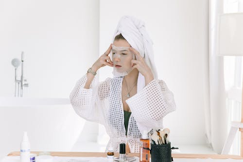 Photo Of Woman Applying Face Mask On Her Face