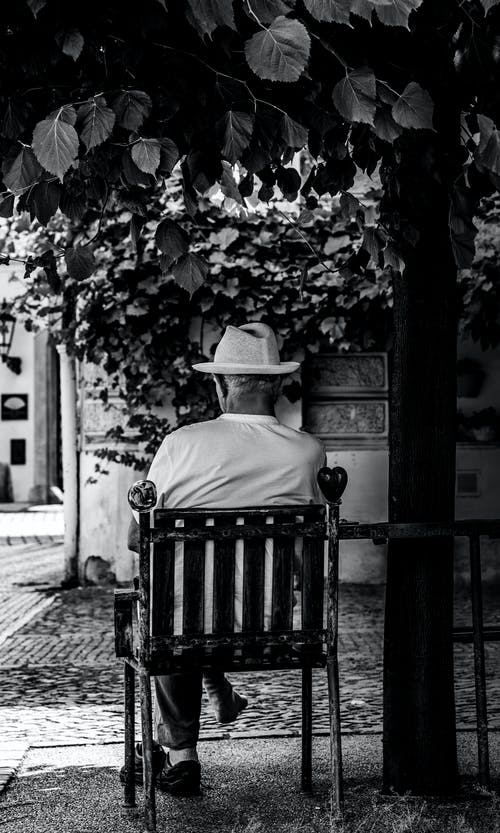 Grayscale Photo of a Man Sitting on a Chair