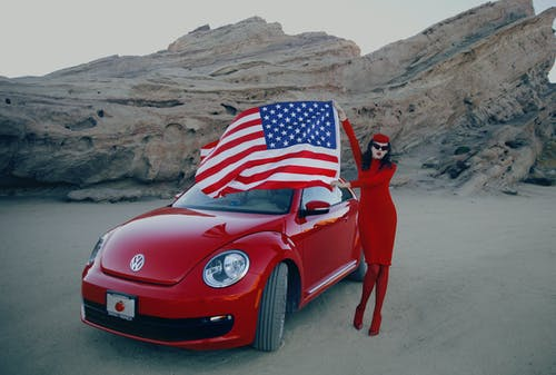 Photo Of Red Car Beside Woman
