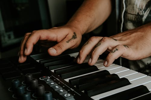 Crop man playing synthesizer at home