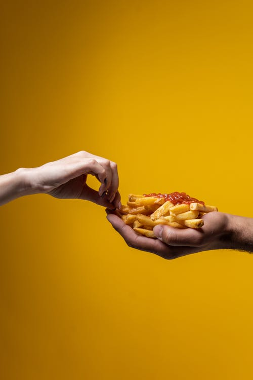 Person Sharing French Fries