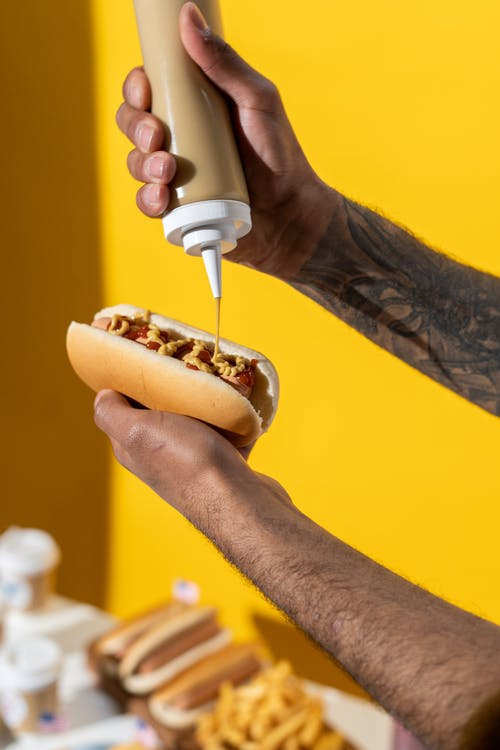 Person Putting Mustard on Hotdog