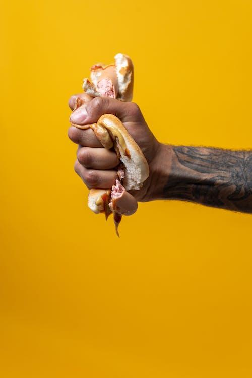 Person Squeezing Hotdog