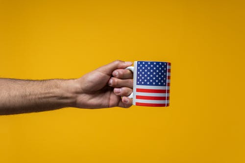 Person Holding a Mug with a US Flag Design