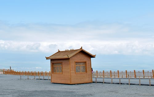 Brown Wooden House on White Sand