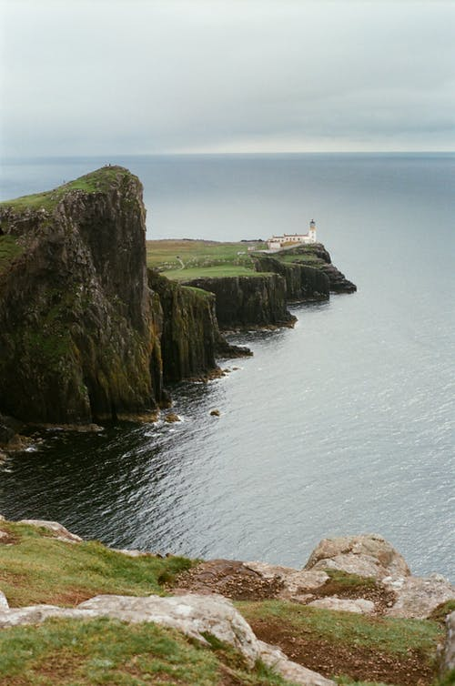 Green and Brown Rock Formation on Sea