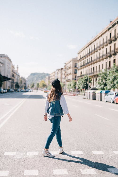 Woman in Blue Denim Jacket and Blue Denim Jeans Crossing The Street