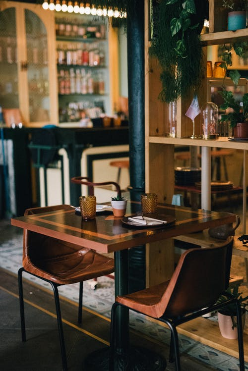 Brown Wooden Table With Empty Glasses And Plates In A Cafe