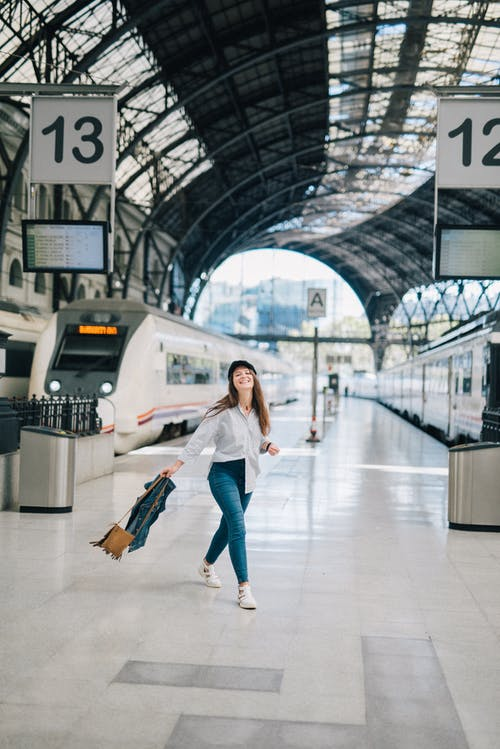 Woman in White Long Sleeve Shirt and Blue Denim Jeans Standing on The Platform Of A Train Station