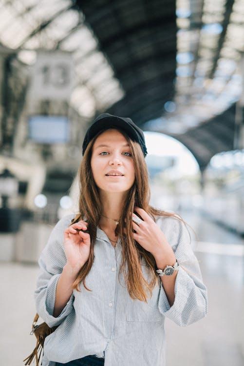 Woman in White Sleeveless Shirt Wearing Black Hat