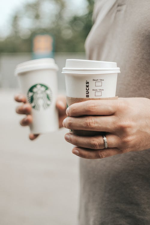Person Holding White Starbucks Cups