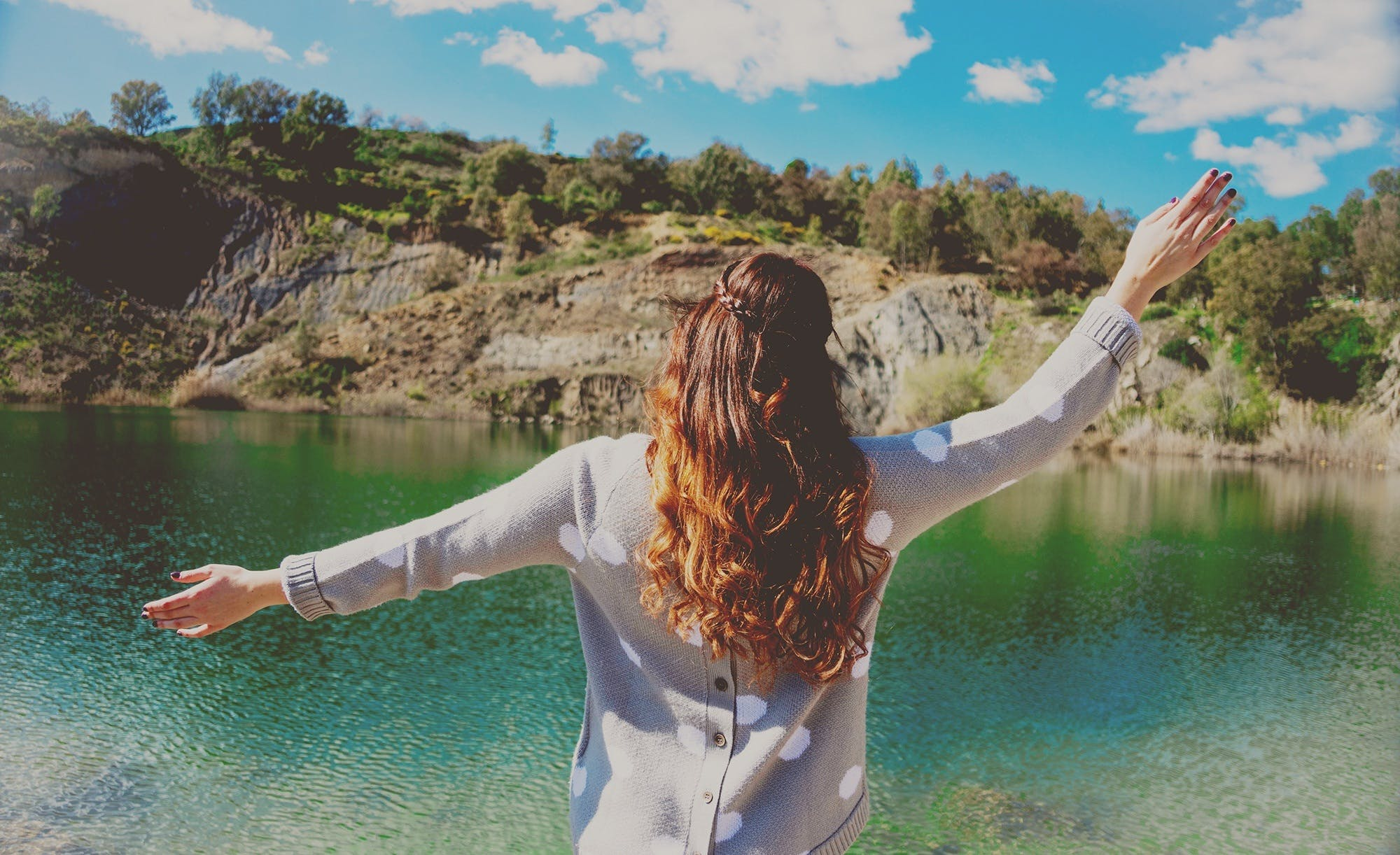 Woman in White Sweater Standing in Front of Body of Water during Day Time
