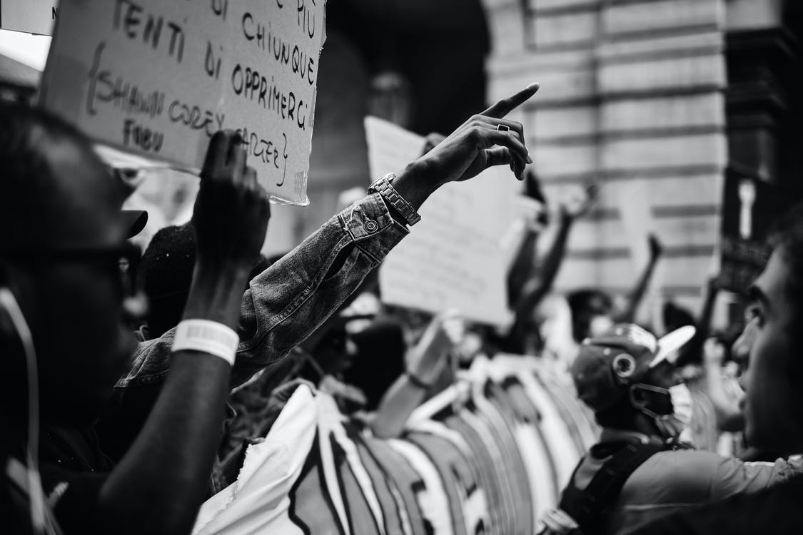 Grayscale Photo of People In A Rally