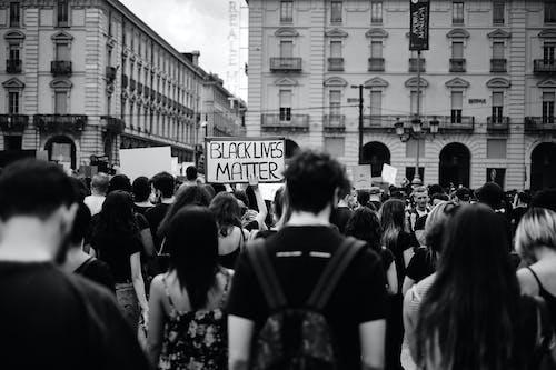 Grayscale Photo of People Rallying on Street