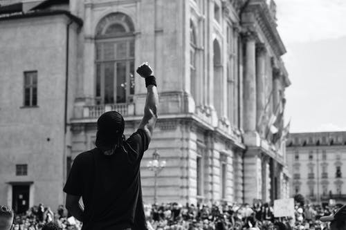 Man in Black T-shirt Standing Infront Of A Crowd In Protest