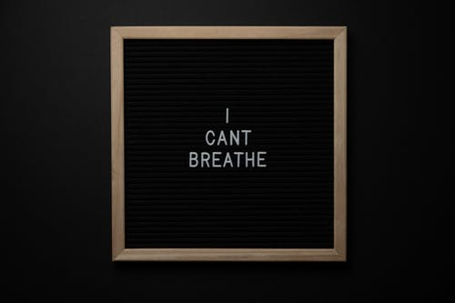 Top view of phrase I Cant Breath on small black signboard with light beige thin frame on black background