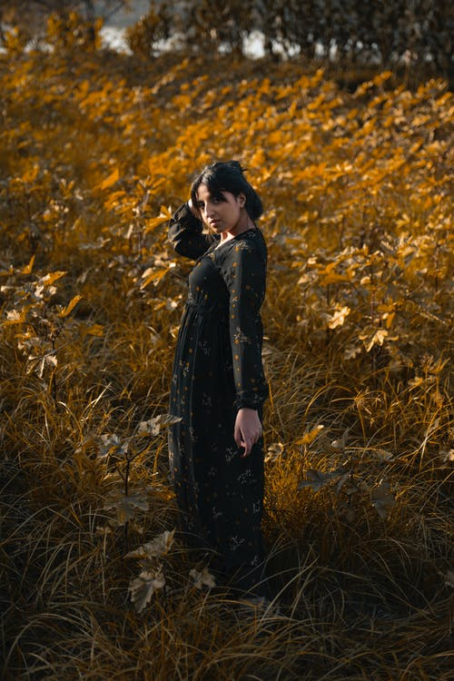 Woman in Black Coat Standing on Yellow Leaves