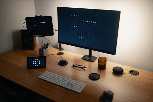 Computer with various electronic devices and speaker placed on table