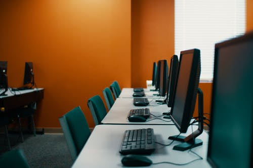 Modern computers with keyboards and mice placed in row on table with chairs  in contemporary workplace with orange walls