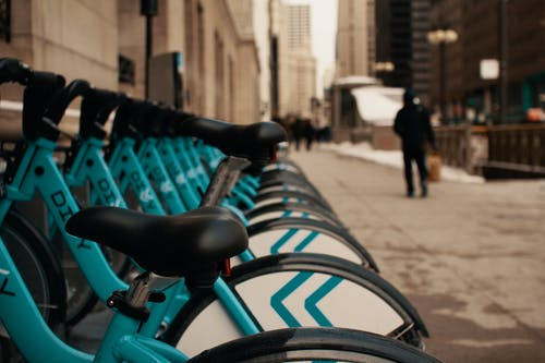 Row of modern similar bicycles parked on street near contemporary building in city on winter day