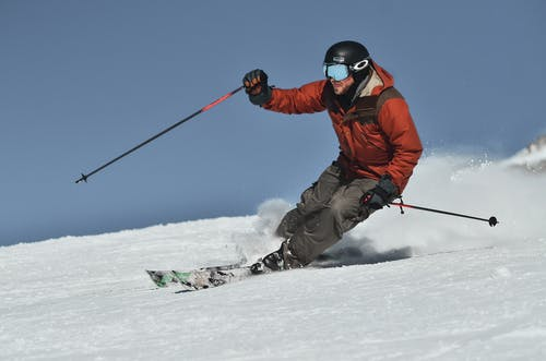 Man in Red Jacket and Black Pants Riding on Snow Ski