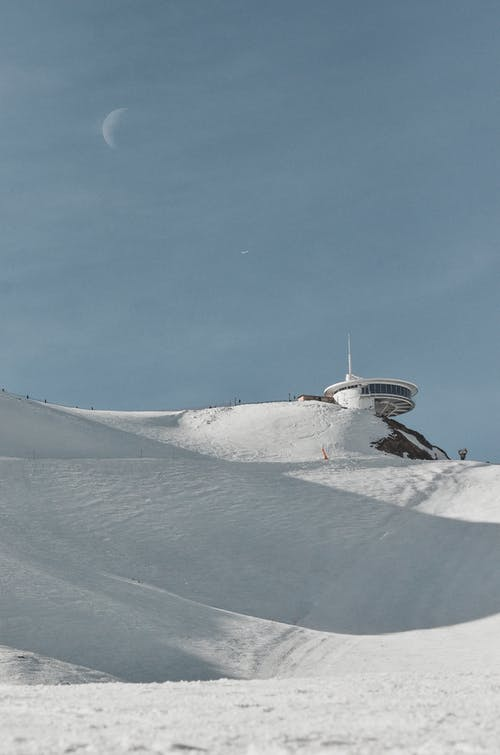 White and Gray Ship on Snow Covered Ground Under Blue Sky