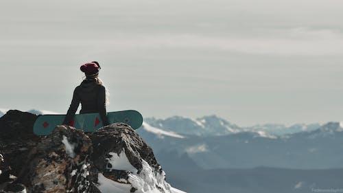 Man in Black Jacket Sitting on Rock Formation
