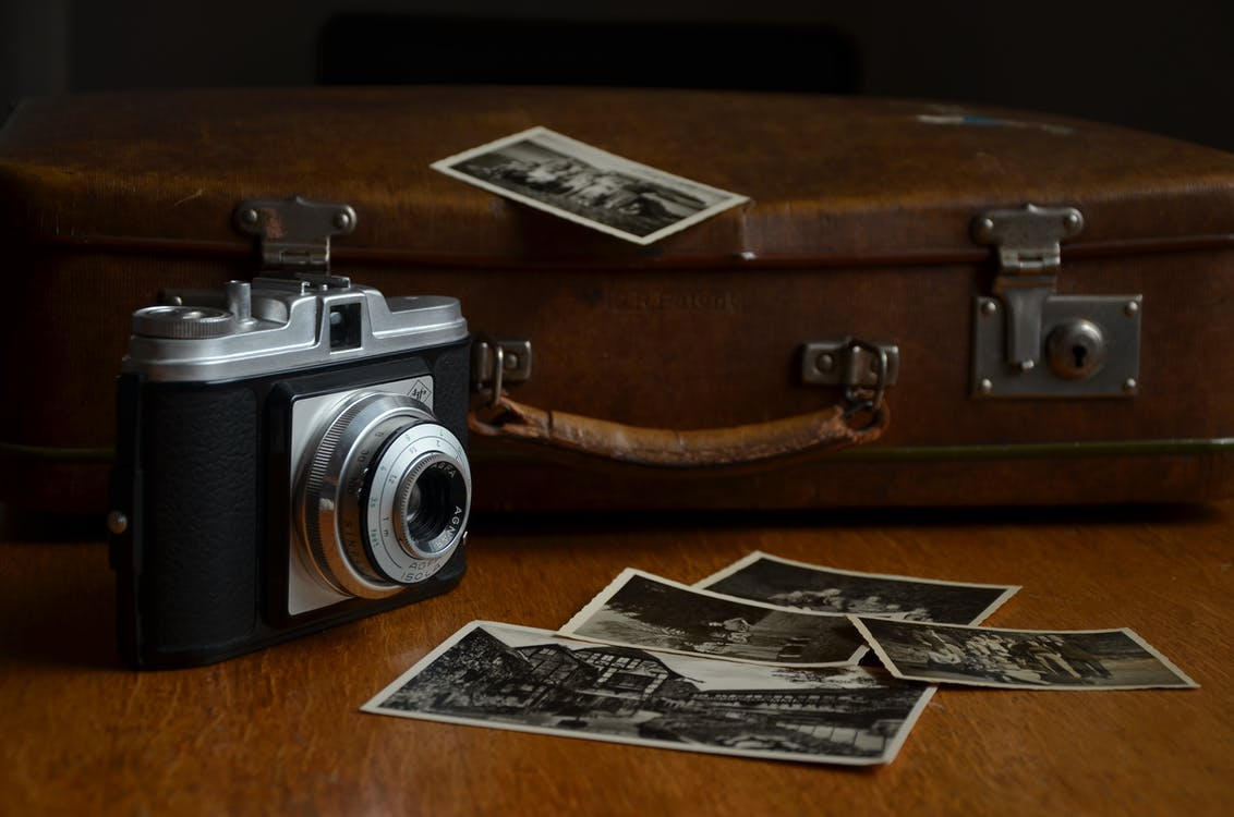 Black and Gray Camera Beside Photos