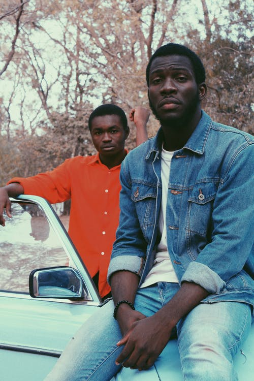 Black men in casual clothes standing near old car