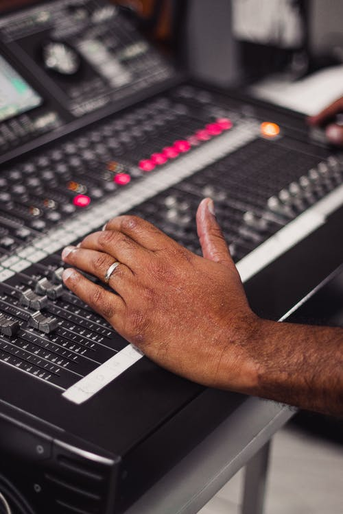 Person Using Black and Gray Audio Mixer