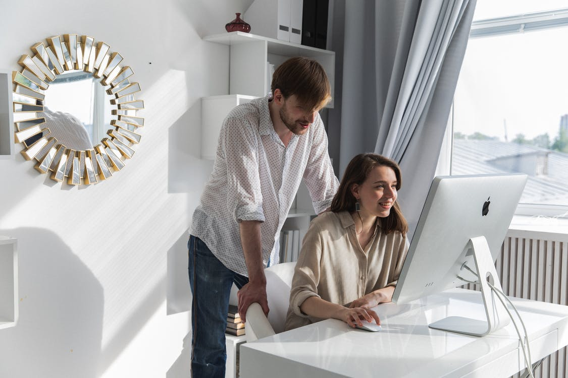 Man and Woman Sitting on White Table
