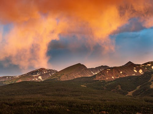 Brown and White Mountains Under Cloudy Sky