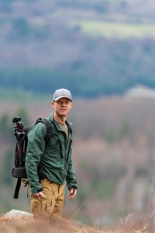 Concentrated man in casual clothes and cap with black backpack with tripod standing on grassy hill and looking at camera