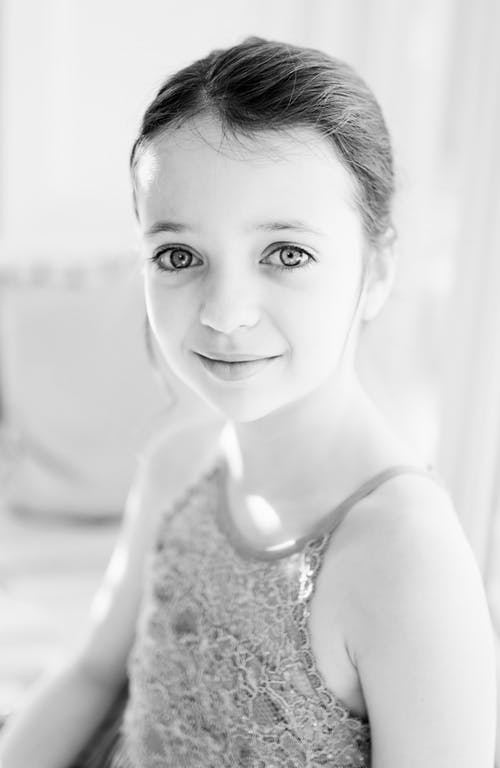 Black and white of young girl with expressive light eyes and dark hair in lace top looking at camera