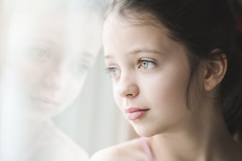 Crop calm young girl with bright expressive eyes and brown hair leaning against window looking out